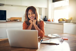 Smiling young female entrepreneur working online in her kitchen