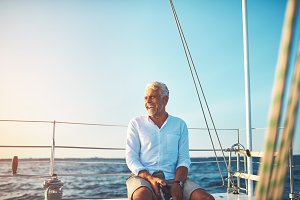 Mature man enjoying a sunny day sailing on the ocean