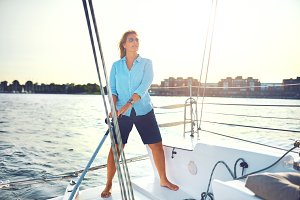 Mature woman standing on her boat steering with the rudder