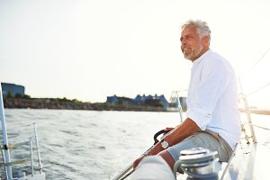 Smiling mature man out sailing on a sunny afternoon