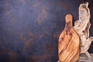 Empty wooden cutting board on old rusty background