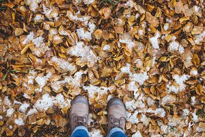 Leather Boots legs View on the Snow with Fallen leaves at autumn fall winter season.