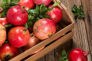 Wooden box full of pomegranates