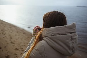 Beautiful young girl in winter jacket looking to winter sunset by river and warms cold hands breathing