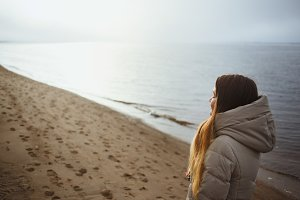 Beautiful young girl in winter jacket relaxing with closed eyes at winter sunset by the river.