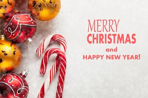 Greeting card with Christmas and new year. The inscription merry Christmas and happy new year on a white concrete background with Christmas tree decorations red and gold balls and candy canes