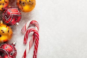Greeting card with Christmas decorations in red and gold balls, snow and candy canes on a white concrete background. Top view. Overhead