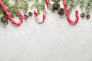 Christmas or New Year decoration background: fir-tree branches, blue balls, cones, candy under the snow on white concrete background with copy space. Top view. Overhead