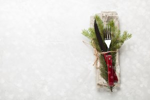 Christmas table. Cutlery with wooden handles and with a sprig of fir tied with string on a white concrete background with copy space. Photo is decorated with snowflakes. Top view.