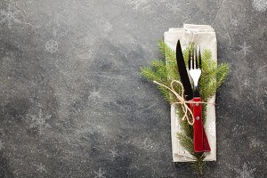 Christmas table. Cutlery with wooden handles and with a sprig of fir tied with string on a dark concrete background with copy space. Photo is decorated with snowflakes. Top view.