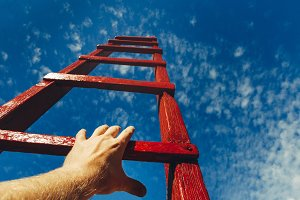 A male hand holds onto the crossbar of a red wooden staircase leading to the blue sky