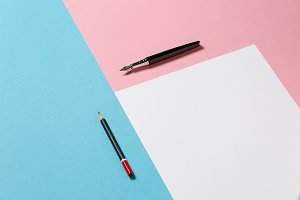 White sheet of paper, a black wooden pencil and an ink pen on a blue and pink surface