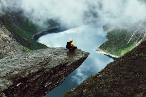 Man sits at the end of Trolltunga