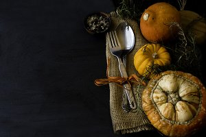 Autumn seasonal table with pumpkins, spoons and fork, space for text, selective focus