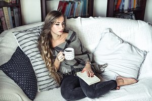 girl reading a book on the couch