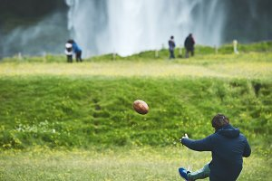 man playing the ball near famous Seljalandsfoss waterfall in southern Iceland