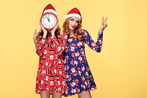 Christmas New Year. Woman in Santa hat with Clock