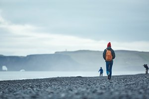 woman walking on Reynisfjara black sand beach, southern Iceland.