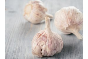 Three garlic bulb close up on gray wooden table