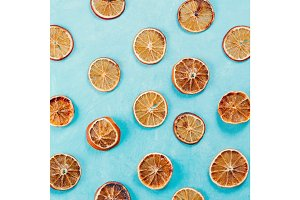 Pattern with dried orange slices on blue concrete background