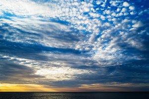 Horizontal vibrant ocean horizon cloudscape background backdrop