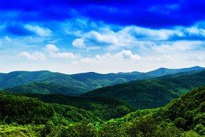 Horizontal vivid fresh hills landscape with cloudscape backgroun
