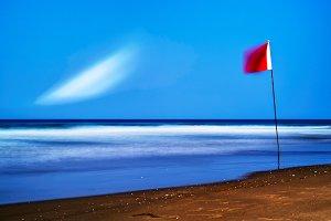Horizontal red flag of freedom beach landscape background