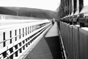 Black and white walking man on Norway bridge background