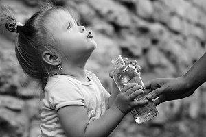 little girl holding a bottle in hand