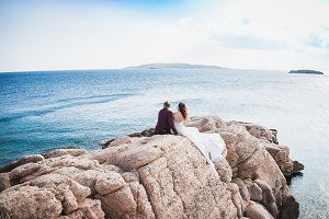 couple sitting on rock from the back over beautiful seascape landscape