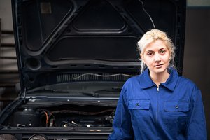 Female Mechanic /apprentice Posing In Front Of A Car