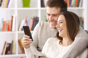 Happy couple using a smart phone