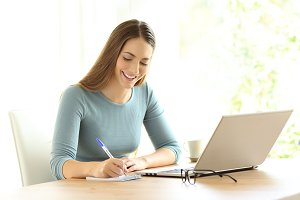 Happy woman writing notes