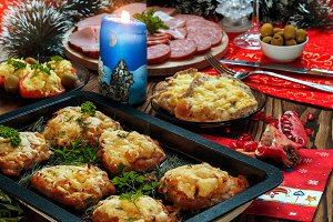 Christmas baked chops with cheese and cold cuts platter, served on the old wooden table