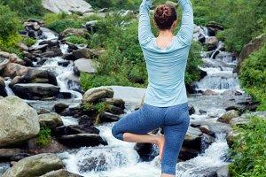Woman in yoga asana Vrikshasana tree pose at waterfall outdoors