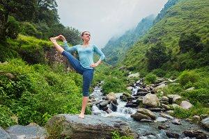 Woman doing Ashtanga Vinyasa Yoga asana outdoors at waterfall