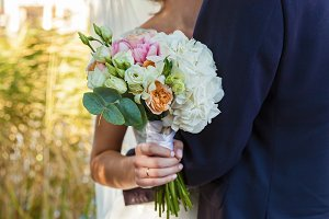 the bride is holding a wedding bouquet