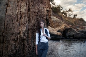 business woman on suit vest and white shirt standing near big stone on the sea cost