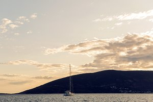 yacht docked at the pier in the Bay of Montenegro at sunset