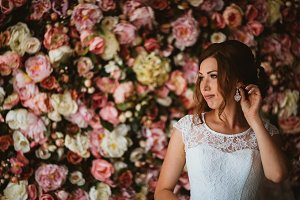 beautiful bride on the background of a wall of flowers