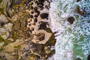 Aerial view looking down at sea waves hitting rocks