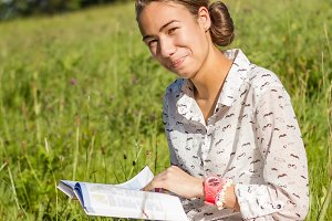 Young student reading a book in park