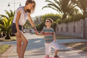 Girl and cute kid with a skateboards