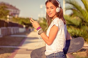 Girl with skate listen music outdoor