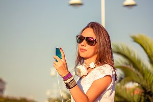 Girl with skate looking smartphone