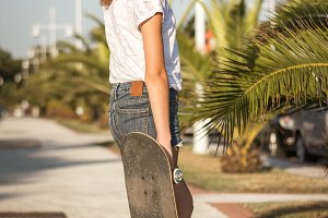 Girl with skateboard on a summer day