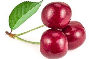 Three ripe red cherries