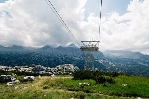 Scenic view of alps mountains a sunny day with cableway on foreg