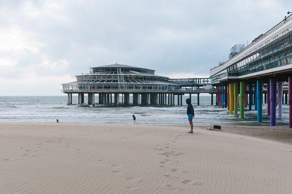 Girl wearing a hoodie near the pier…