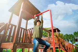 curious fearless little girl climbing on playground alone in sunny weather